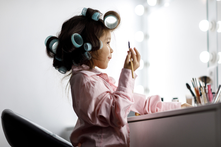 Photo pour Cute little girl playing with her mothers cosmetic - image libre de droit