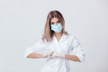 Photo pour Portrait of woman doctor with face mask wearing white medical gloves - image libre de droit