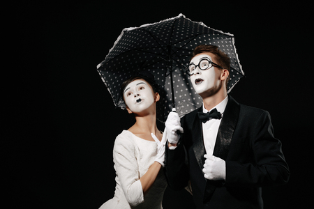 Photo pour portrait of surprised couple mime with umbrella on black background. man in tuxedo and glasses and woman in white dress - image libre de droit