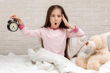 Photo for cute surprised little child girl in pyjamas with clock in bed. good morning - Royalty Free Image