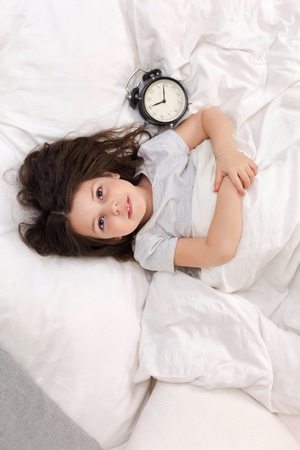 Photo for cute little child girl in pyjamas with clock in bed. good morning. top view - Royalty Free Image