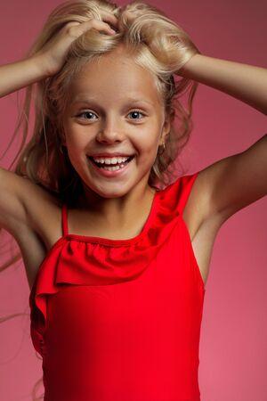 Photo pour Portrait of surprised happy cute little blonde baby girl on a pink background - image libre de droit