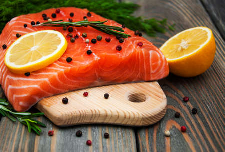 Foto de salmon fish with fresh herbs,  lemon and pepper - Imagen libre de derechos