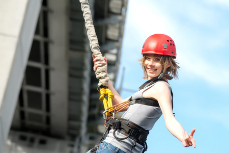 beautiful young woman in a helmet hanging on a rope after the bungee jump against the sky