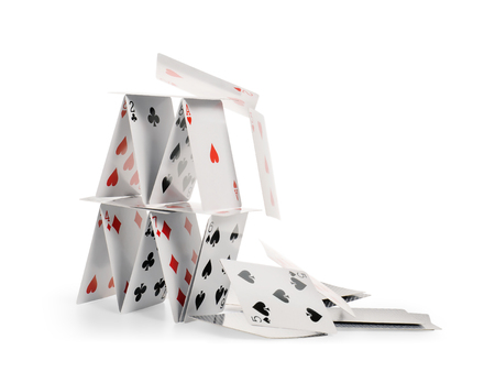 Foto de Crashed house of cards. Falling cards isolated on white, clipping path included - Imagen libre de derechos