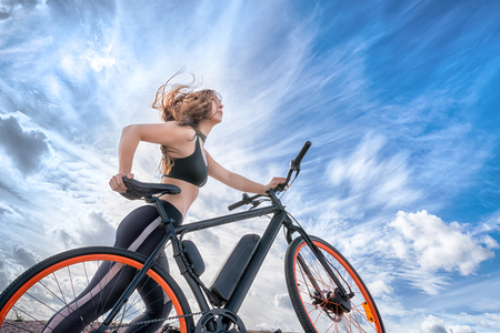 Photo pour Athletic girl with hair flying in the wind leading electric bike. Outdoor portrait against blue cloudy sky - image libre de droit