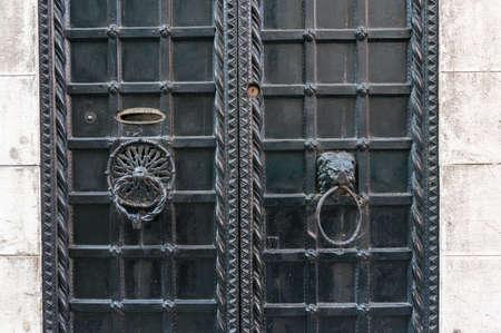 Photo pour Closed old metal door with cast iron lattice and metal door handles, knockers - image libre de droit