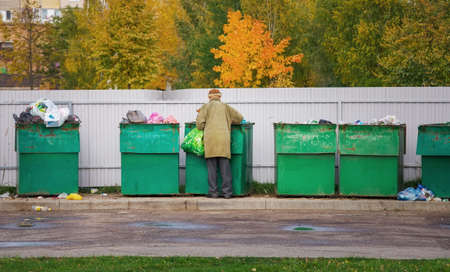 Photo for Poor homeless old man searching in garbage in autumn time. Men rummaging in trash container looking for food and reusable goods - Royalty Free Image