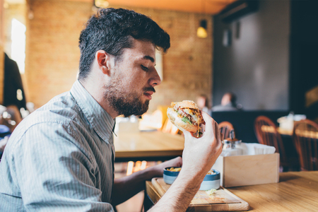 Foto per Studen is eating in a room and enjoying fast food - Immagine Royalty Free