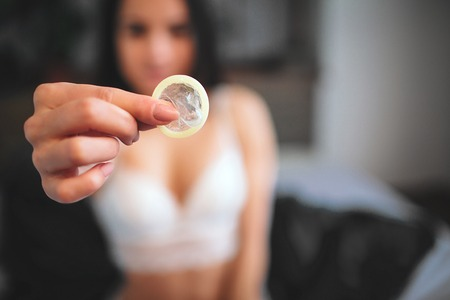 Photo for Woman showing a condom on bed, Focus on the condom in the foreground - Royalty Free Image