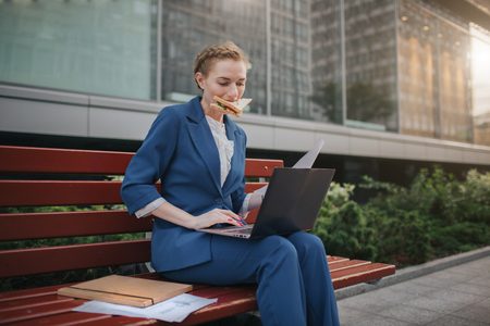 Foto de Worker eating and working with documents on the laptop at the same time. Businesswoman doing multiple tasks. Multitasking business person. - Imagen libre de derechos