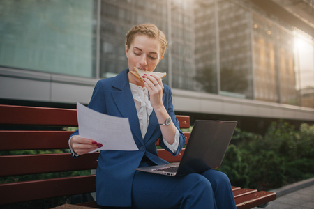 Foto de Busy woman is in a hurry, she does not have time, she is going to eat snack outdoors. Worker eating and working with documents on the laptop at the same time. Businesswoman doing multiple tasks. Multitasking business person. - Imagen libre de derechos