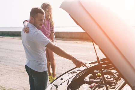 Photo for Handsome father teaching his school age daughter to change motor oil or repairing family car. - Royalty Free Image