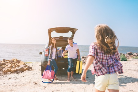 Foto de Young couple standing near the opened car boot with suitcases and bags. Dad, mom and daughter are traveling by the sea or the ocean or the river. Summer ride by automobile - Imagen libre de derechos