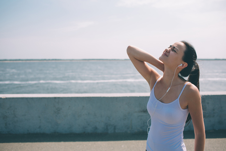 Photo pour Neck pain during training. Athlete running Caucasian black hair woman runner with sport injury and touching upper back muscles outside after exercise workout in summer - image libre de droit