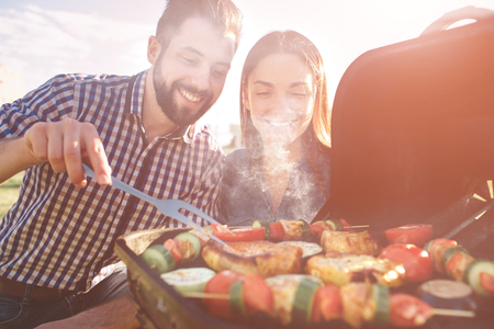 Photo pour Friends making barbecue and having lunch in the nature. Couple having fun while eating and drinking at a pic-nic - Happy people at bbq party. - image libre de droit