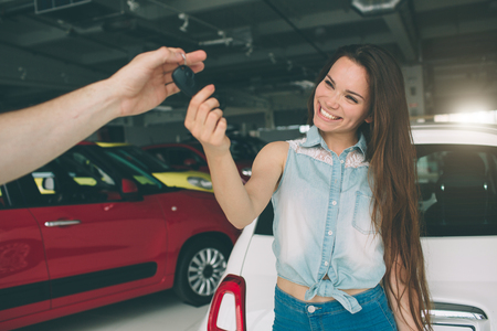 Photo pour Beautiful young woman is holding a key in car dealership. Auto business, car sale, - happy female model in auto show or salon - image libre de droit