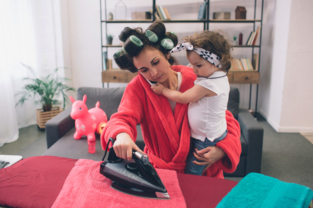 Photo pour mother and baby together engaged in housework Ironing clothes . Housewife and kid doing homework. Woman with little child in the living room. Homemaker doing many tasks while looks after her infant - image libre de droit