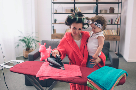 Foto de mother and baby together engaged in housework Ironing clothes . Housewife and kid doing homework. Woman with little child in the living room. Homemaker doing many tasks while looks after her infant - Imagen libre de derechos