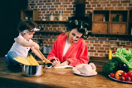Photo pour Stressed mum at home. Young mother with little child in the home kitchen. Woman doing many tasks while looks after her baby - image libre de droit