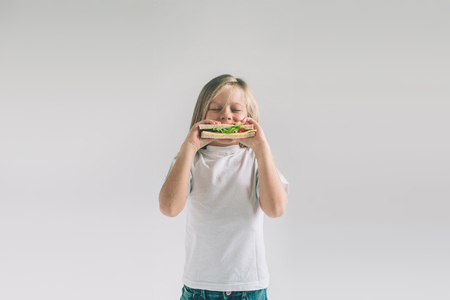 Foto de Child holding a piece of hamburger. Kid eats fast food. not helpful food. very hungry baby. Girl isolated on white background. - Imagen libre de derechos