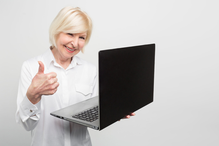 Photo pour Old but modern woman is holding a new laptop. She likes to use it. The lady prefers to know evetything about new technologies and the last news about computer equipment. Isolated on white background. - image libre de droit