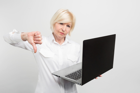 Photo pour A picture of mature lady with new laptop. She has tested it and admitted the laptop is bad. Thats why she shows a big thumb down. Isolated on white background. - image libre de droit