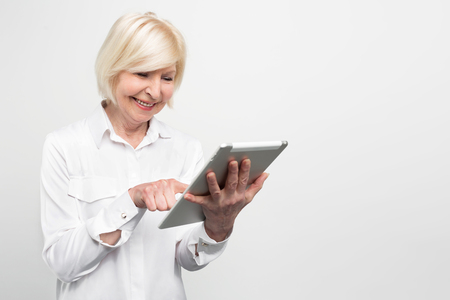 Photo pour Old but happy woman is using a brand new tablet. She is testing it because she likes new technologies. Isolated on white background. - image libre de droit