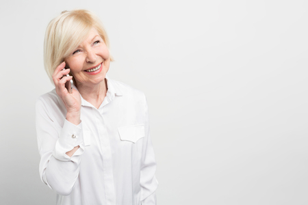 Photo pour Nice picture of a lady calling t his family using a new smartphone. She adores new technologies and like to try to use new devices as much as she can. Isolated on white background. - image libre de droit