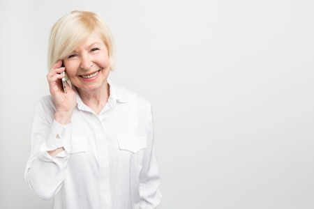 Photo pour A picture of old lady using new phone. She likes to test it. This phone is her favourite one. Isolated on white background. - image libre de droit