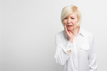 Photo for Old lady is suffering from a toothache. It started to ache suddenly. She needs to go to dentist. Isolated on white background - Royalty Free Image