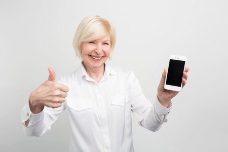 Photo pour A picture of mature woman with new smartphone. She has tested it and admitted this phone is a good one. Thats why she shows a big thumb up. Isolated on white background. - image libre de droit