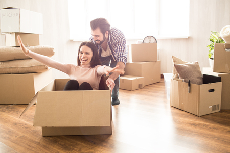 Foto de Attractive woman is sitting on the box. Her man is pushing her so she can ride. This people look happy and satisfied - Imagen libre de derechos