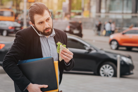 Foto de Busy man is in a hurry, he does not have time, he is going to eat snack on the go. Worker eating, drinking coffee, talking on the phone, at the same time. Businessman doing multiple tasks. Multitasking business person. - Imagen libre de derechos