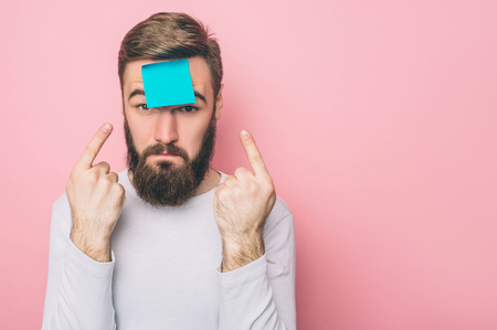 Photo pour Strange guy has put a blue sticker on his forehead. He is pointing at it with fingers on both hands. Isolated on pink background - image libre de droit