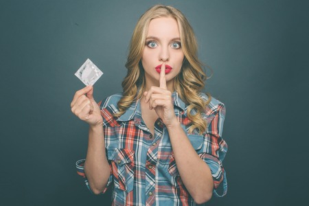 Foto de Girl is holding a condom in her hand and showing the silence symbol. She looks very serious. Isolated on blue background. - Imagen libre de derechos