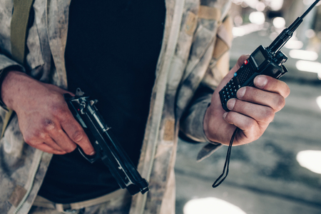 Photo for Close up of soldiers hands. There is a portable radio in left hand and black pistol in right one. Guy wears black shirt and uniform on top of it. Cut view. - Royalty Free Image