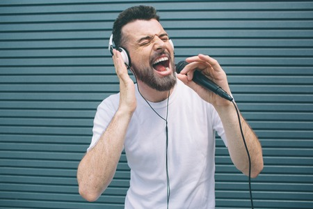Photo pour Happy musician is enjoying listening to music. He wears headphones and singing. Guy is using karaoke. Man is singing ot loud. Isolated on striped and blue background. - image libre de droit