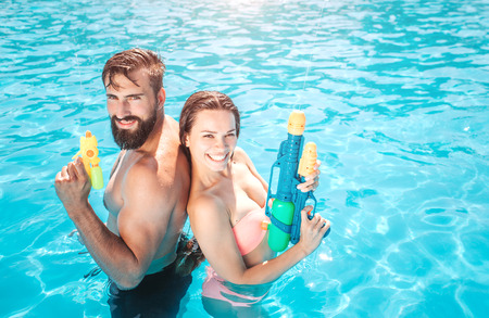 Photo for Godd-looking man and woman stand in swimming pool and look on camera. They pose and smile. People hold water gun in hands. They are ready to shoot. - Royalty Free Image