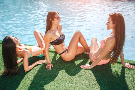 Photo for Three delightful models sit on grass at edge of swimming pool. One gets tan from sun. Other two look at each other and smile. Young women have fun. They relax. - Royalty Free Image