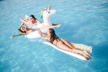 Photo for Three young models swimming in pool. They lying on floats. Friends have fun. They chilling and splashing water. Models look fantastic, sexy and hot. - Royalty Free Image