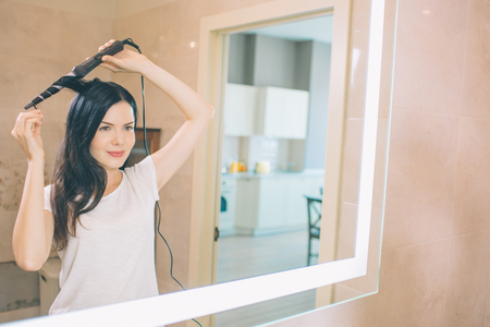 Photo pour Brunette stands at mirror and using curler hair. She is in bathroom. Woman holds curler with both hands. She makes hair dressing. - image libre de droit