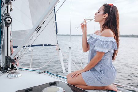 Photo pour Stunning young woman sits at edge of yacht and drinks champaigne. She keeps eyes closed. Woman is alone. She enjoyes spending time like that. - image libre de droit