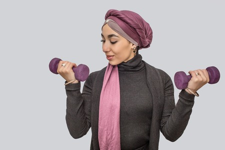 Photo for Strong young arabian woman exercising with dumbbells. She looks at one of it. She wears hijab. Isolated on grey background. - Royalty Free Image