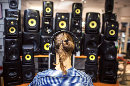 Photo for Guy with long ponytail sit in front of sound speakers. There are lots of it in room. Young man is alone. - Royalty Free Image