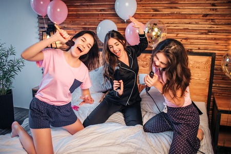 Photo for Playful and nice young women stnding on knees on bed in room. They pretend singing in microphones. Models hold makeup brush, spray can and hair equalizer in hands. - Royalty Free Image