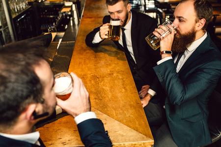 Foto de Young businessman in suit drink bear in bar. They sit in front of each other - Imagen libre de derechos
