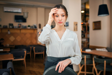 Photo pour Frustrated young waitress look down. She hold tray in left hand. Right one hold on forehead. Young woman stand alone in restaurant - image libre de droit