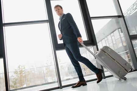 Foto de Young confident buisnessman walking down hall. He has luggage. Man is in airport. - Imagen libre de derechos