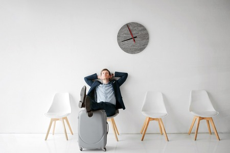 Foto de Relaxed young man sit on white chair in room alone. He wait for flight. Guy hold legs on suitcase. Young man lean to wall. - Imagen libre de derechos